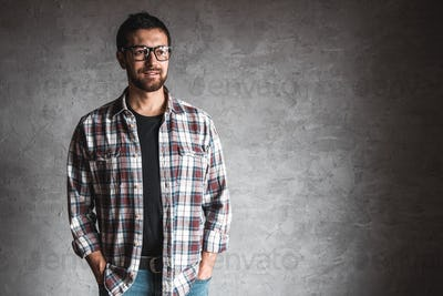 Men in a plaid shirt on a background of gray concrete wall
