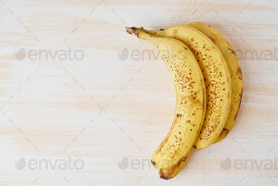 Ripe bananas with brown spots on bright white wooden table, copy space, top view