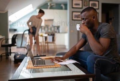 Black freelancer using laptop while girlfriend tidying living room