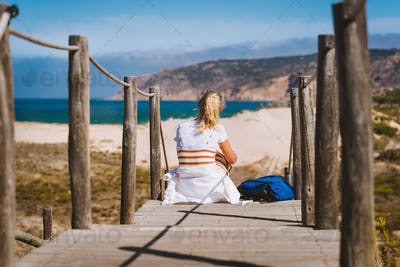 Adult female tourist sitting on path leading to Praia do Guincho Beach. Cascais, Portugal. This is