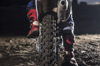 Close up of motocross wheel on the background of the track while driver sitting on the bike