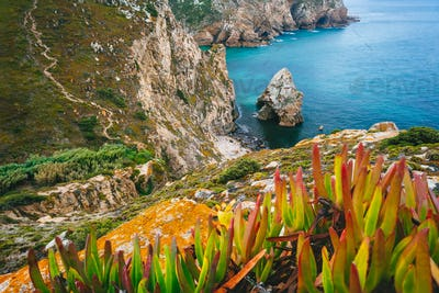 Cabo da Roca is the extreme point of Europe. Hidden beache with Rock, blue clear waters and foliage