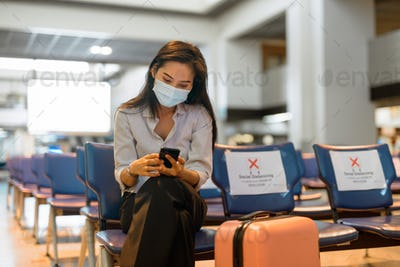 Young Asian tourist woman with mask using phone and sitting with distance at the airport