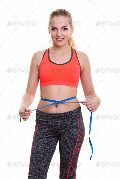 Studio shot of young happy teenage girl smiling while measuring
