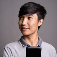 Young Asian man using mobile phone against gray background