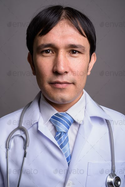 Young Asian man doctor against gray background