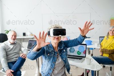 Group of seniors with VR goggles on computer and technology education class