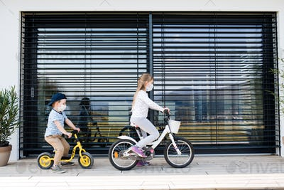 Small girl and boy with bicycles outdoors at home. Corona virus and quarantine concept