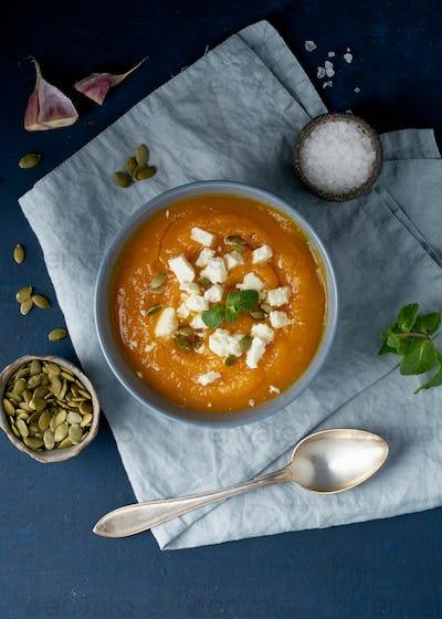 Pumpkin cream soup with feta cheese, autumn homemade food, dark blue background