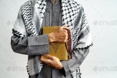 male gesture holding quran and prayer beads
