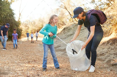 Adult Team Leader With Group Of Children At Outdoor Activity Camp Collecting Litter Together