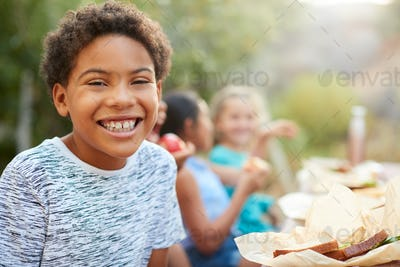 Portrait Of Boy With Friends Eating Healthy Picnic At Outdoor Table In Countryside