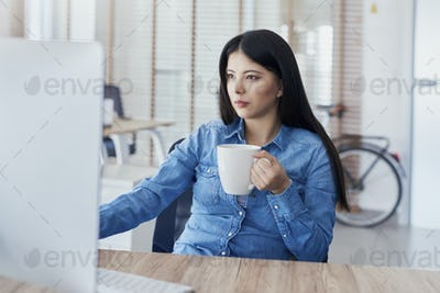 Asian woman drinking coffee and working on computer