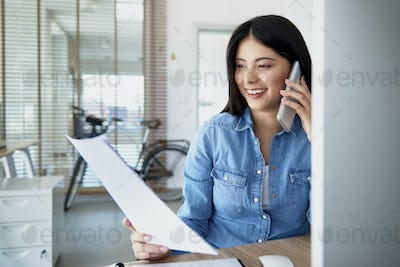 Cheerful Asian woman in the office talking on the phone