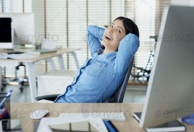 Satisfied Asian woman having a break in the office