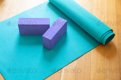 Yoga mat and exercise bricks on wooden floor, pilates yoga class concept