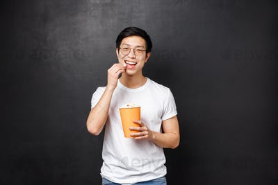 Portrait of carefree good-looking asian male attend cinema, pleased smiling and eating popcorn