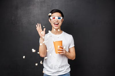 Leisure, movies and lifestyle concept. Portrait of amused and carefree funny asian guy in t-shirt