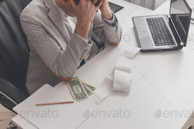 Young man frustrated at his house by debt