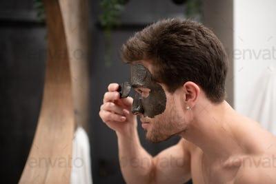 Glad man applying mud mask in bathroom