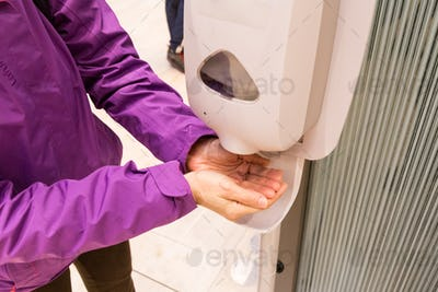 Person cleaning hand with anti-bacterial diinfectant sanitizer in public mall