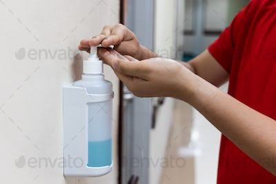 Person dispensing disinfectant sanitizer liquid onto hand in hospital