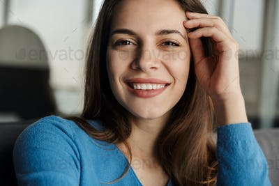 Image of woman looking at camera and smiling while sitting on sofa