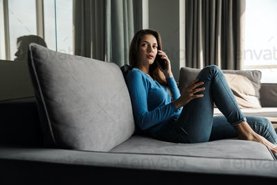 Image of serious woman talking on cellphone while sitting on sofa