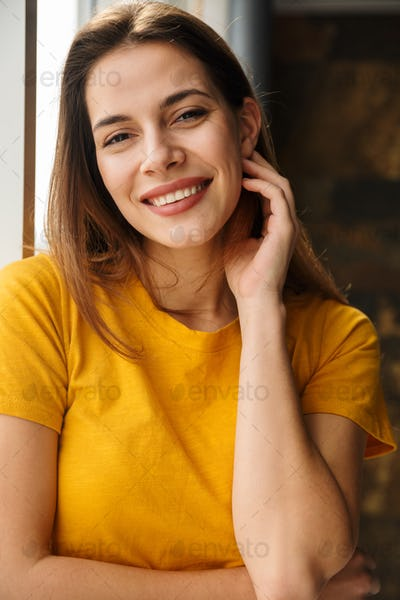 Image of pleased woman looking at camera and smiling while standing