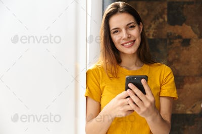 Image of pleased woman using mobile phone and smiling while standing