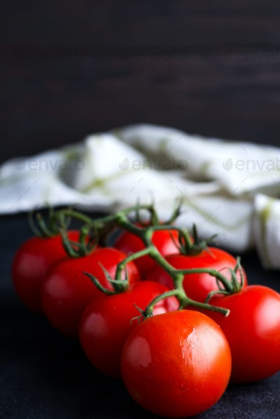 Fresh ripe organic tomatoes branch on a dark background with textile towel