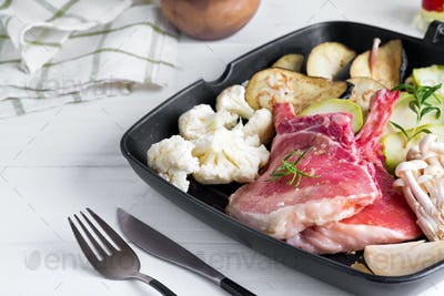 Ceramic plate with fresh raw ingredients meat and vegetables for cooking dinner on a white wooden
