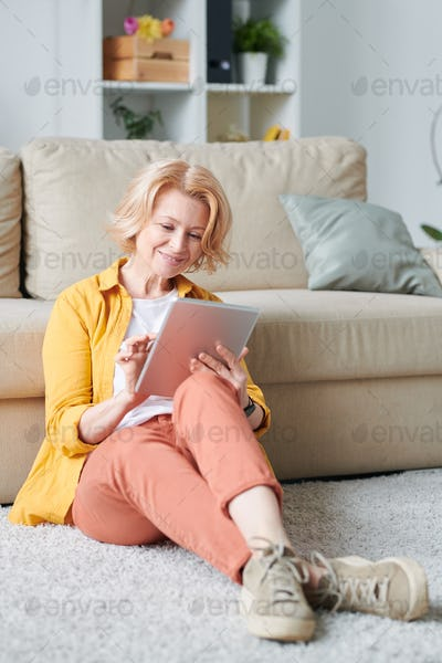 Mature relaxed businesswoman with mobile gadget sitting on the floor by couch