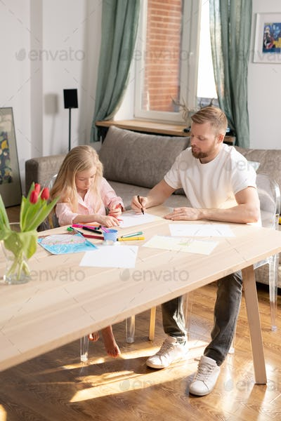 Young man with crayon over blank paper helping his cute little daughter to draw
