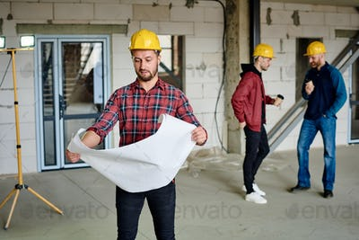 Young builder in hardhat and casualwear looking at sketch in blueprint