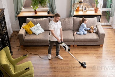 Young man cleaning floor of living-room while his daughter playing on couch