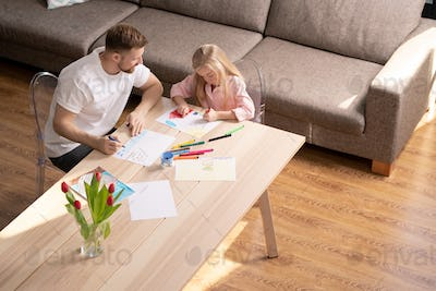 Cute little girl drawing house on paper with her father sitting near by