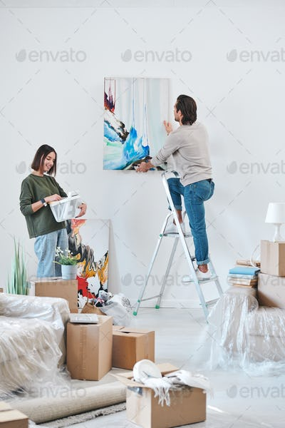 Young man standing on stepladder by wall and hanging abstract painting