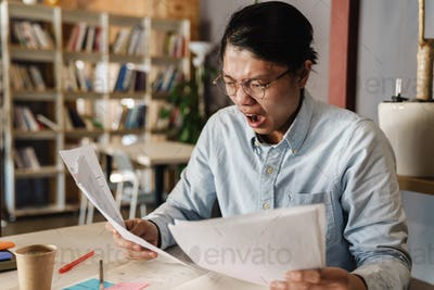 Image of displeased asian man expressing shock while doing homework