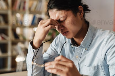 Image of tired asian man with headache rubbing holding eyeglasses