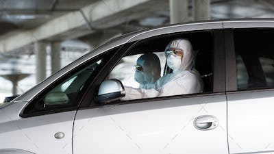 Medical workers in coronavirus suits driving a car and looking for sick people