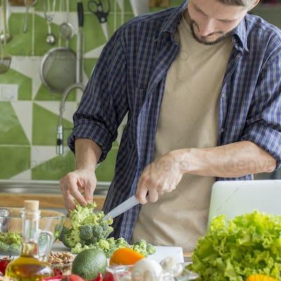 Young man preparing Vegetable Salad In Bowl