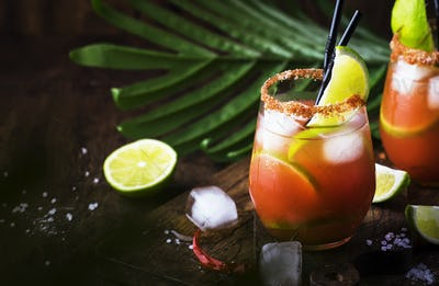 Michelada - Mexican alcoholic cocktail with beer, lime juice, tomato juice, spicy sauce