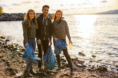 Portrait of young volunteers standing at beach
