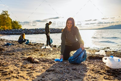 Smiling young woman cleaning beach with volunteers during sunset
