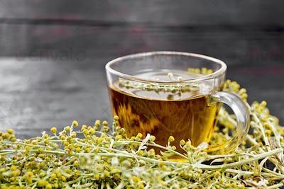 Tea of gray wormwood in glass cup on dark board