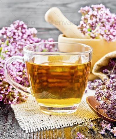 Tea of oregano in cup with mortar on dark board