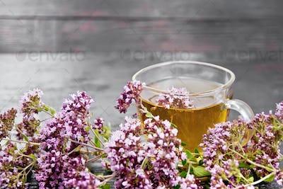 Tea of oregano in glass cup on board
