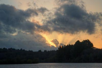 Sunset twilight rays pierce cumulonimbus clouds
