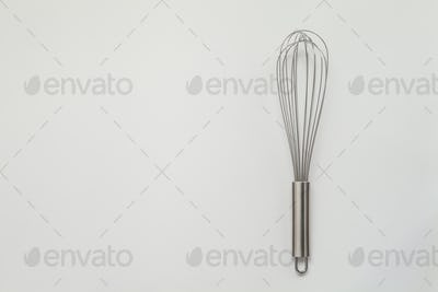 Metal whisk for whipping on a white background